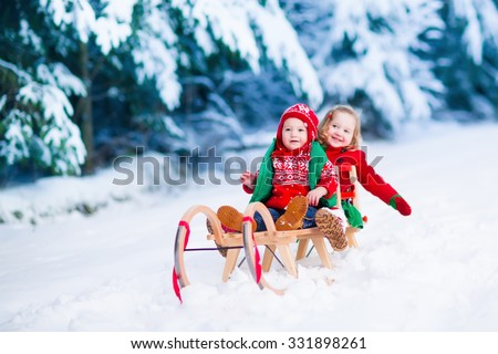 Little girl and boy enjoy a sleigh ride. Child sledding. Toddler kid riding a sledge. Children play outdoors in snow. Kids sled in Alps mountains in winter. Outdoor fun for family Christmas vacation. - stock photo