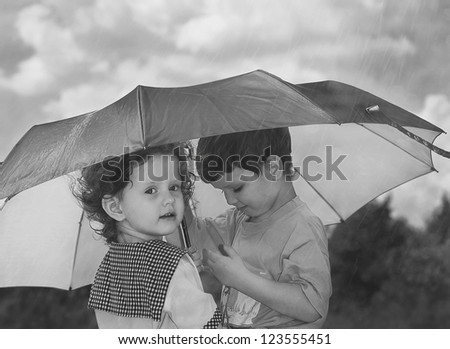 little girl and boy hiding under an umbrella from the rain, black and white photo - stock photo