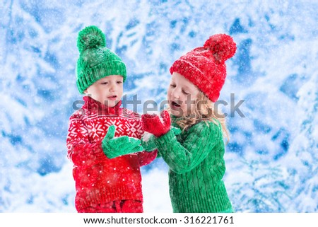 Little girl and boy in red and green knitted hat catching snowflakes in winter park on Christmas eve. Kids play outdoor in snowy winter forest. Children catch snow flakes on Xmas. Toddler kid playing. - stock photo