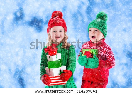 Little girl and boy in red and green knitted hat holding Christmas present boxes in winter park on Xmas eve. Kids play outdoor in snowy winter forest. Children opening presents. Toddler kid with gifts - stock photo