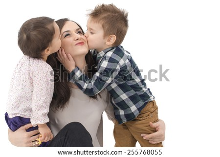 little girl and boy kissing their mother - stock photo