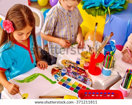 Little girl and boy  painting picture by brush on table in  kindergarten .  - stock photo