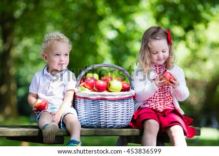 Little girl and boy play in apple tree orchard.  - stock photo