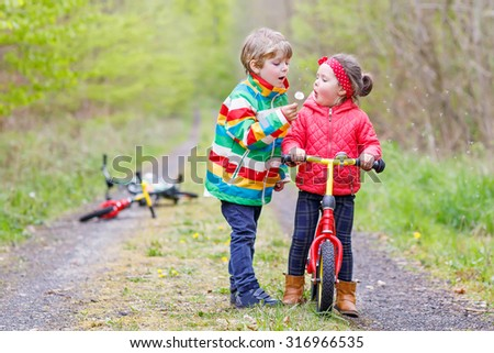 Little girl and boy playing together in forest in bright jackets on a rainy day with bikes. Friendship between siblings. Happy family concept  - stock photo
