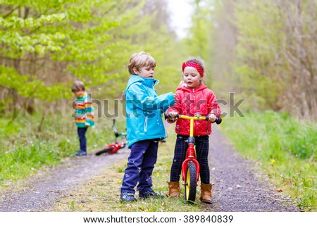 Little girl and boy playing together in forest in bright jackets on a rainy day with bikes. Children blowing dandelion flowers. Friendship between siblings. - stock photo