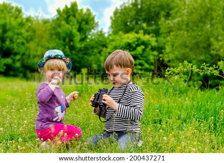 Little girl and boy playing with binoculars sitting in a green grassy field as they enjoy an educational day exploring and learning about nature