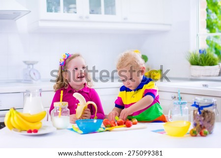 Little girl and boy preparing breakfast in white kitchen. Healthy food for children. Child drinking milk, eat fruit. Happy smiling preschooler kids enjoy morning meal, cereal, banana and strawberry. - stock photo