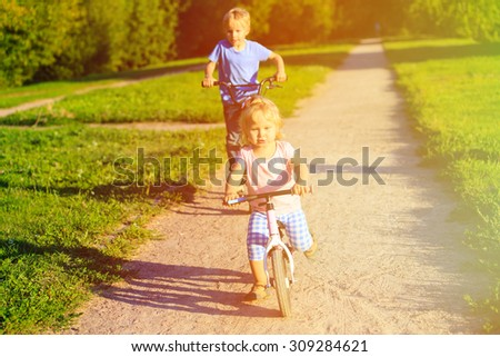 little girl and boy riding bikes in summer park, kids competition and sport - stock photo