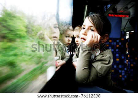 little girl and boy travel on a train - stock photo