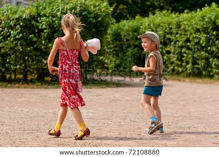 Little girl and boy walking in park - stock photo