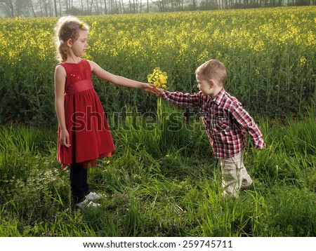 Little girl and boy with bouquet of dandelions - stock photo