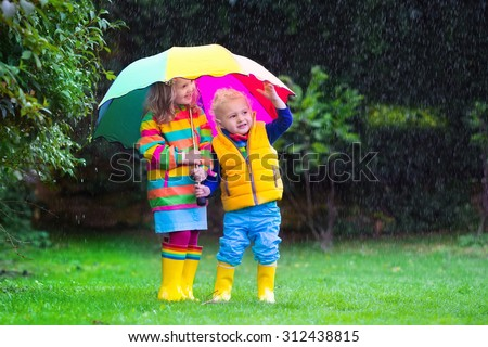 Little girl and boy with colorful umbrella playing in the rain. Kids play outdoor by rainy weather in fall. Autumn fun for children. Toddler kid in raincoat and boots walk in the garden. Summer shower - stock photo