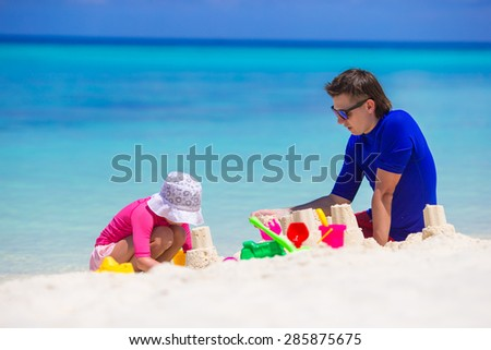 Little girl and dad playing with beach toys on summer vacation