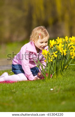 Little girl and daffodils in park - stock photo