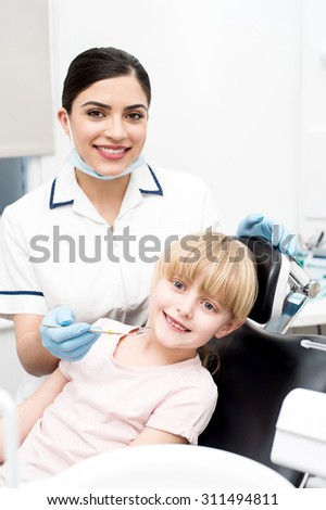 Little girl and dentist posing to the camera