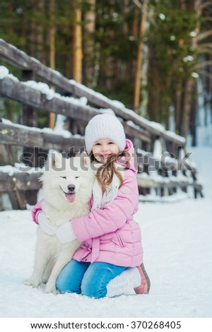 Little girl and dog Samoyed winter outdoors