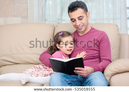 Little girl and father are enjoying reading book together