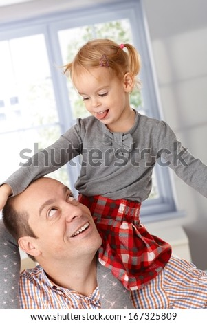 Little girl and father having fun, playing together, little girl sitting on father's shoulder.