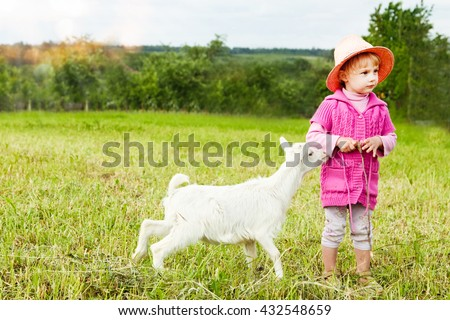 Little girl and goat kids on the spring meadow