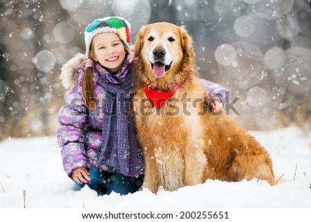 little girl and golden retriever looking at the camera - stock photo