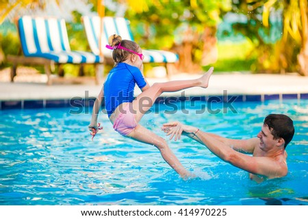 Little girl and happy father having fun in outdoors swimming pool - stock photo