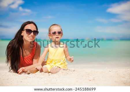 Little girl and happy mom having fun at exotic beach on sunny day - stock photo
