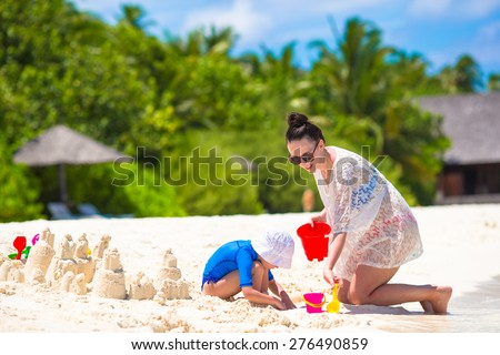 Little girl and happy mother playing with beach toys on summer vacation - stock photo