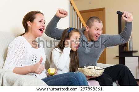 Little girl and happy parent sitting with popcorn in front of TV. Focus on girl - stock photo
