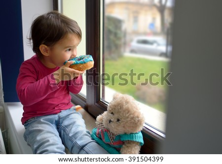 little girl and her bear toy eating  donuts - stock photo