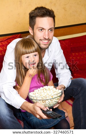 Little girl and her borther enjoy eating popcorn and watching tv at home - stock photo
