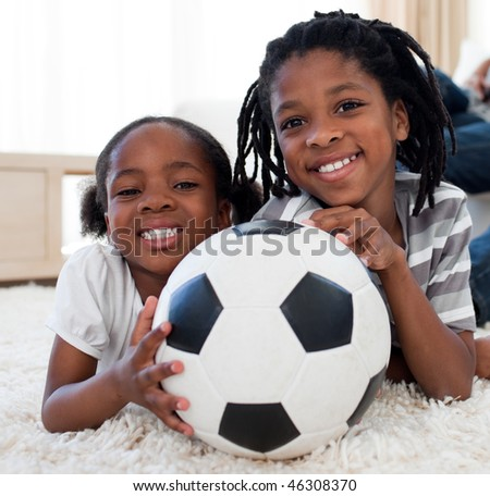 Little girl and her brother holding soccer ball lying on the floor - stock photo