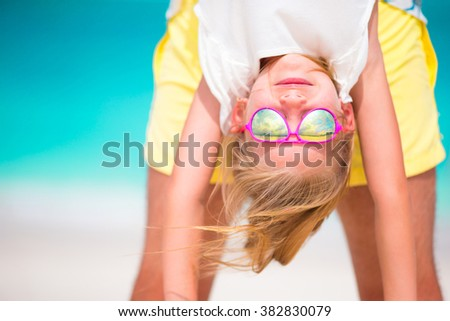 Little girl and her dad enjoy summer vacation at perfect beach - stock photo
