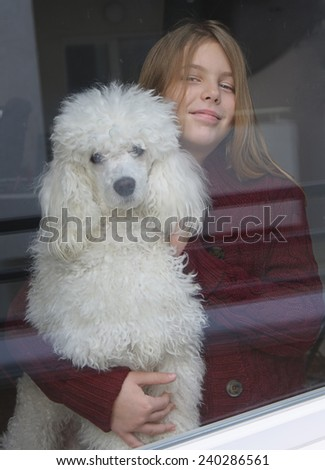 Little girl and her dog looking out the window - stock photo