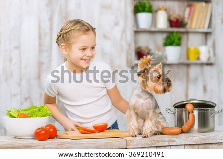 Little girl and her dog on the kitchen table.  - stock photo