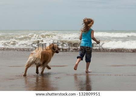 little girl and her dog running into the ocean - stock photo