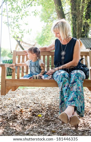 Little girl and her elderly mother are sitting on the bench in the park and having fun. - stock photo