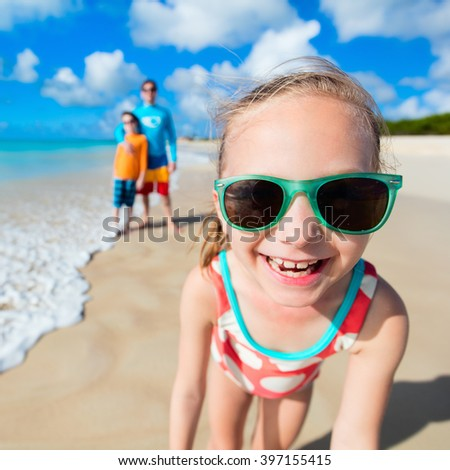 Little girl and her family father and brother enjoying beach vacation on Caribbean