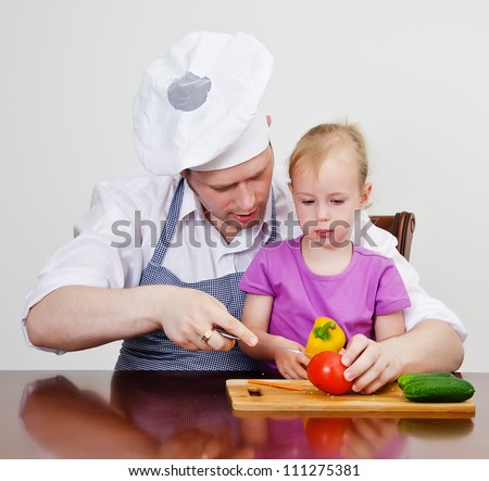 Little girl and her father cutting vegetables in the kitchen