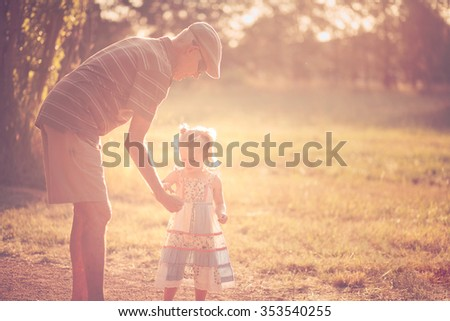 Little girl and her grandfather spending time in a park - stock photo
