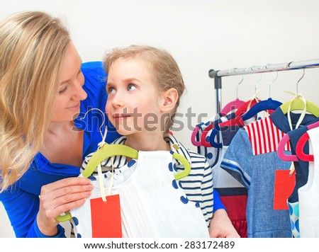 Little girl and her mom choosing dress in clothing store. - stock photo