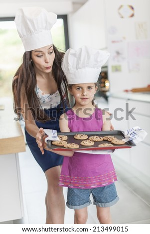 little girl and her mom offering a tray of cookies - stock photo