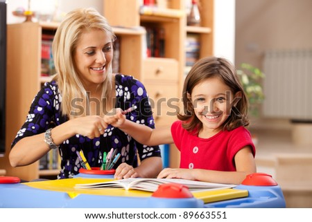little girl and her mother drawing on a book and having fun at playtable - stock photo
