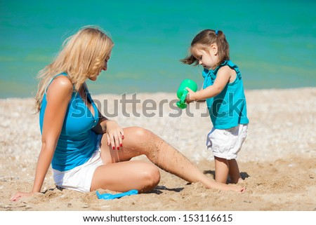 little girl and her mother have a good time at the beach - stock photo