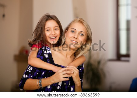 little girl and her mother holding and laughing, family moment