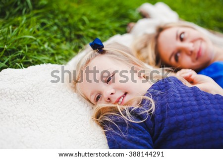 Little girl and her mother on picnic lying on plaid looking sidewards. Both smile and wear blue dresses. mother on background while daughter in focus. Copy space - stock photo