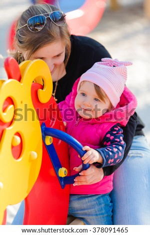 Little girl and her mother on the playground