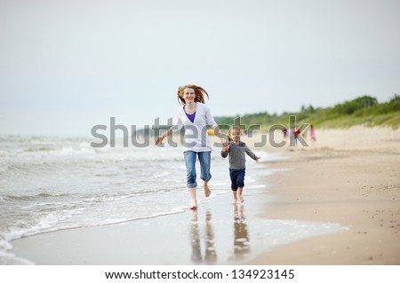 Little girl and her mother playing on the beach - stock photo