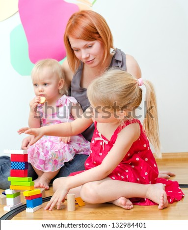 Little girl and her mother playing with railway sitting on the floor - stock photo