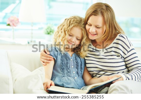 Little girl and her mother reading book together - stock photo