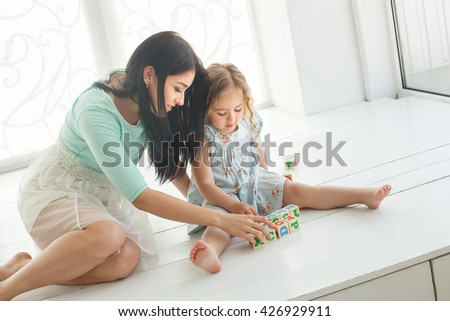 Little girl and her mother sitting on the floor with abc cubes - stock photo
